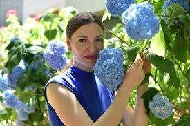 Plave hrizanteme i žena u plavoj haljini među njima, dizajnerka nakita Daniela Komatović